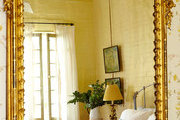 An ornate, gilded mirror in an antique-filled New Orleans bedroom