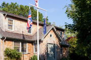A trio of flags hung outside a shingle-clad home