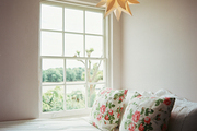 A paper star-shaped lantern above a bed with floral pillows