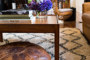 A vintage leather pouf and wooden coffee table on a Beni Ourain rug