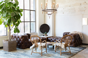 Tufted sectional and fur padded chairs under chandelier.