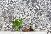 A detail of decor items on a credenza in front of gray and white wallpaper.