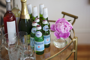 A bar cart topped with bottles of Pellegrino and wine