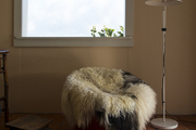 A tactile fur throw and a modern floor lamp in a guest room
