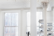Tall white pillars in a large window-lit room.