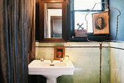 Vintage green tile and a white pedestal sink contrasted with black accents