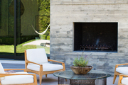Chairs around a glass-topped coffee table by a patio's outdoor fireplace