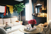 A black living space brightened by art and neutral furniture