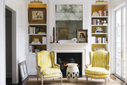 Two armchairs upholstered in yellow flanking a garden stool in front of a fireplace mantel in a sitting room with French doors