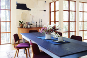 A dining room with a blue table and purple upholstered Thonet chairs
