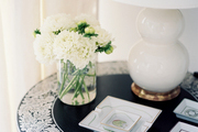 A round side table with a white lamp and a vase of flowers