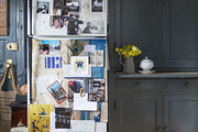 A refrigerator turned mood board in a dark-painted kitchen