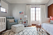 Tonal nursery with patterned area rug and contemporary furniture.