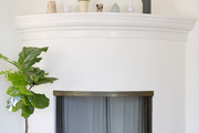 A series of vessels atop a fireplace mantel