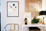 Layered artwork on a white console beside a gold chair