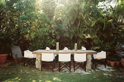 A rustic table and a set of chairs in an outdoor dining space