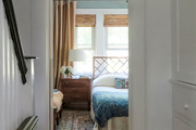 A look inside of a blue, brown, and white bedroom from the hall.