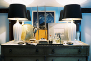 A pair of white lamps with black shades on a green dresser