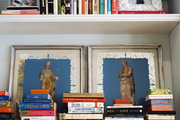 Stacks of books and framed art on white shelves