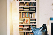 A leather butterfly chair and a paper lamp in front of a white bookcase