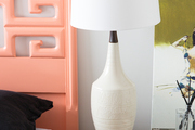 A detail of a nightstand with a white lamp.