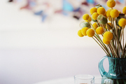 A vase of yellow flowers on a marble tabletop in a breakfast room