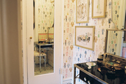 A dressing room with wallpaper featuring paper dolls