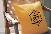 A cane chair with a yellow pillow bearing Veuve Clicquot's initials