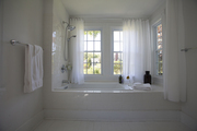 Opaque curtains hanging in the all white window lit bathroom.