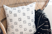 A detail of a black and white pillow and throw on a wicker chair.