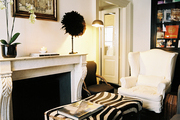 A zebra-print ottoman with a pair of white wingback chairs