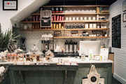 White subway tile and open wooden shelving in a coffee bar