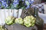 Artichokes and blooms on a tabletop display at Napa Valley's Poor House