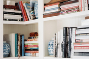 White built-in bookcases decorated with books, a clock, and blue-and-white ginger jars