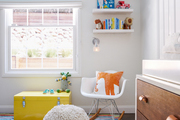 Window-lit nursery with kids toys and fun furniture.