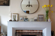 A round mirror over a brick fireplace and white mantle