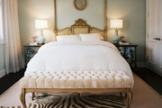 A zebra-hide rug and a tufted bench at the foot of a vintage bed