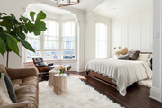 Large bay window and tall wainscot above white bedding.