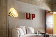 A bedroom with a white daybed, frescoed ceilings, block letters used as art, and a contemporary floor lamp