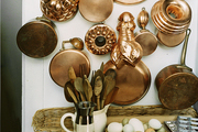 A collection of copper cookware hung in a kitchen
