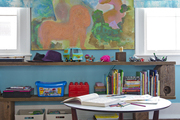 Shelves of toys and a low table in a kids' bedroom