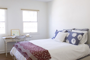 A wooden writing desk beside a bed dressed in white linens and a printed quilt