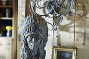 An antique bust atop a console.
