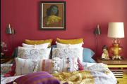 Patterned decor pillows on a multi colored bed set.