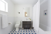 A contemporary bathroom with white walls and a blue and white tile floor.