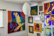 Colorful paintings of women hung up around a room.