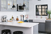 Contemporary kitchen with white countertops and white tiled walls.