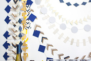 A bar set againts a backdrop of homemade paper garlands created using geometric shapes in varying patterns and colors