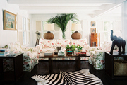 A floral couch and armchairs and a zebra rug in a living space
