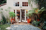 French doors opening onto an outdoor patio with a bistro chair and orange planters